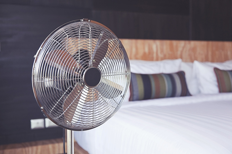 Old electric fan near the bed in the room